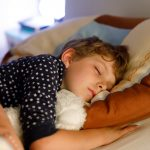 Little preschool kid boy sleeping in bed with colorful lamp. School child dreaming and holding plush toy.